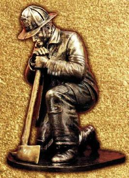 Cast bronze fireman kneeling with ax